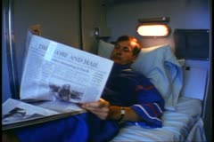 "Man reads newspaper, Globe & Mail, in train berth, on ""The Canadian"" Stock Footage"