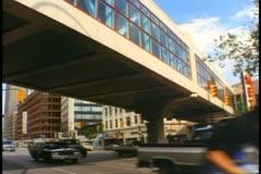 Enclosed pedestrian bridge, traffic passing, Winnipeg, Canada, 1990 Stock Footage
