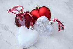 red and white heart ornaments in snow - stock photo