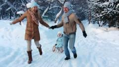 Young parents running, and ride your child on a sled Stock Footage