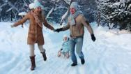 Stock Video Footage of Young parents running, and ride your child on a sled (SLOW)