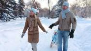 Stock Video Footage of Young couple sledding his child on a sledge in winter park (SLOW)