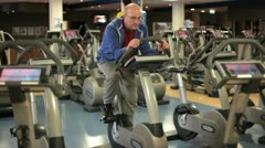 In a gym working out a bald man cycles on a hometrainer Stock Footage