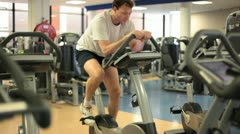 In a gym working out white man cycling on home trainer Stock Footage