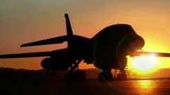 B1-bomber pan silhouetted by the sun as heat ripples off the tarmac - stock footage
