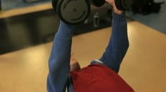 In a gym working out lifting dumbbells Stock Footage