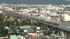 Shinkansen bullet train rides through urban landscape in Japan Stock Footage