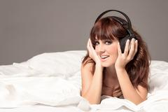 smiling woman in lingerie and headphones on the bed - stock photo