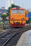 red yellow deisel engine train locomotive approaching to bangkok railway stat - stock photo