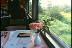"""""""The Canadian"""" train Dining Car, flowers on table, scenery passing Stock Footage"""