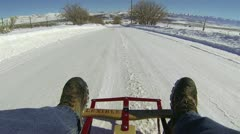 Man sled riding down winter ice snow rural road HD Stock Footage