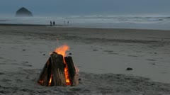 Beach Bonfire with Large Rock in Ocean Stock Footage