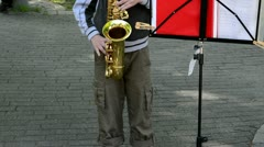 Child play saxophone people walk. street music day Stock Footage