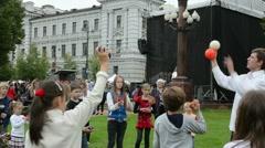 Man teach kids how throw juggling balls vilnius lukiskes square Stock Footage