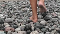 Detail of guy legs walking in the gravel on the beach Stock Footage