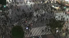 Pedestrians cross the Shibuya intersection in Tokyo at night Stock Footage