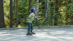 Boy learning to ride on rollerskates Stock Footage