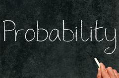 a math teacher writing probability on a blackboard. - stock photo