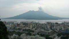Sakurajima volcano behind Kagoshima cityscape in Southern Japan Stock Footage