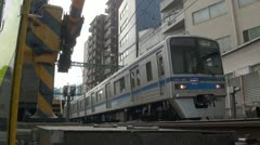 Low angle video of local commuter train riding through Tokyo suburbs Stock Footage