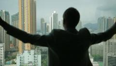 Man opens curtains on the view Hong Kong 3 Stock Footage