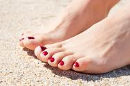 Womans feet on sand Stock Photos