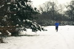 Lone runner in wintry wood, slow motion shot at 240fps, crane shot Stock Footage