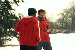 Runner with instructor in a wintry wood, slow motion shot at 240fps, crane shot Stock Footage