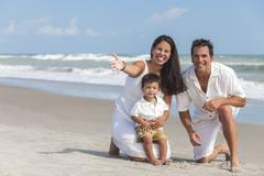 mother, father & boy child family having fun at beach - stock photo
