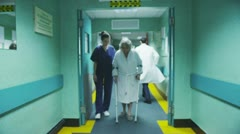 Stock Video Footage of Young female medic helps an elderly patient to take a walk