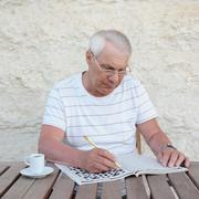 Elderly man with a crossword puzzle Stock Photos