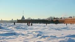 People walking over ice on Neva river near Petropavlovskaya fortress Stock Footage