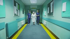 Two female medics help an elderly patient to take a walk  Stock Footage