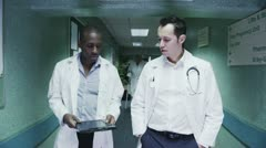 Two male doctors discuss a patient's notes as they walk  Stock Footage