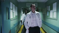 Two male doctors walking and chatting Stock Footage