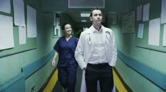 Nurse and doctor chat as they walk along hospital corridor - stock footage