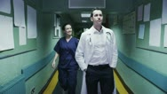 Stock Video Footage of Nurse and doctor chat as they walk along hospital corridor
