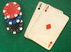 Two vintage aces and poker chips. Stock Photos