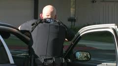 Police Officer Stands Behind Patrol Car Door Stock Footage