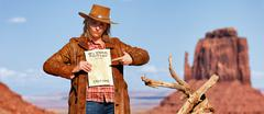 panoramic view of bad cowgirl with wanted paper - stock photo