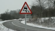 Traffic passing slippery road surface warning sign in snow united kingdom Stock Footage