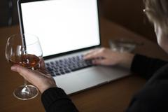 drinking while working on laptop - stock photo