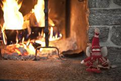 Winter puppet near a fireplace Stock Photos