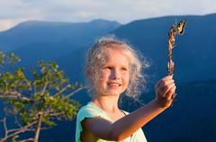 girl and butterfly in sunset mountain - stock photo