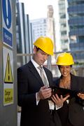 Male and female construction site managers having a meeting Stock Photos