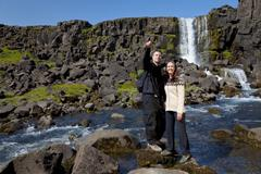 romantic couple man and woman by a waterfall - stock photo