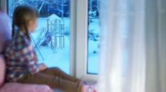Girl looking out the window at the snow-covered playground Stock Footage