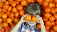 Girl orange. Happy child lying in oranges. Girl looking at camera Stock Footage