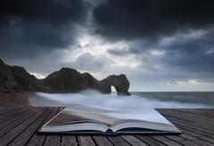 pre-dawn durdle door on jurassic coast in england in pages of book - stock photo