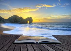 Vibrant sunrise over ocean with rock stack in foreground in pages of book Stock Photos
